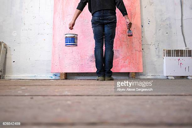 Surface view of male artist standing in front of canvas