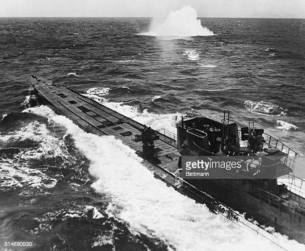 A surfaced German Uboat is under attack by American B25 Mitchell and B24 Liberator bombers A few minutes after this photograph was taken the vessel...