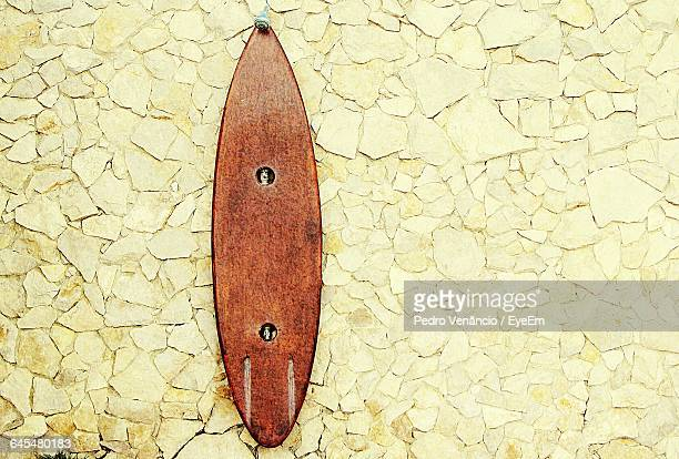Surfboard Hanging On Stone Wall