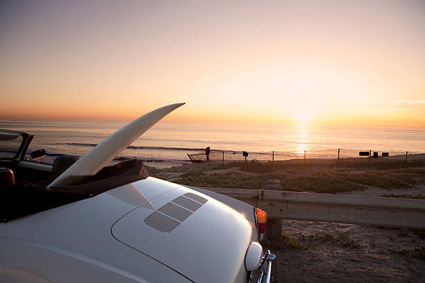 Surfboard in convertible car next to ocean