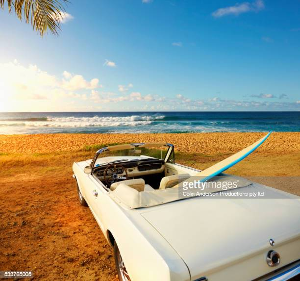 Surfboard in convertible on tropical beach