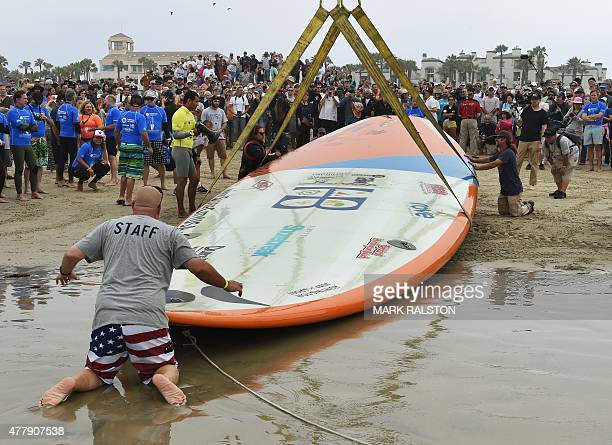 A surfboard is taken to the water as sixty six surfers from Huntington Beach prepare to break the 'Guinness Book of Records' record for the largest...