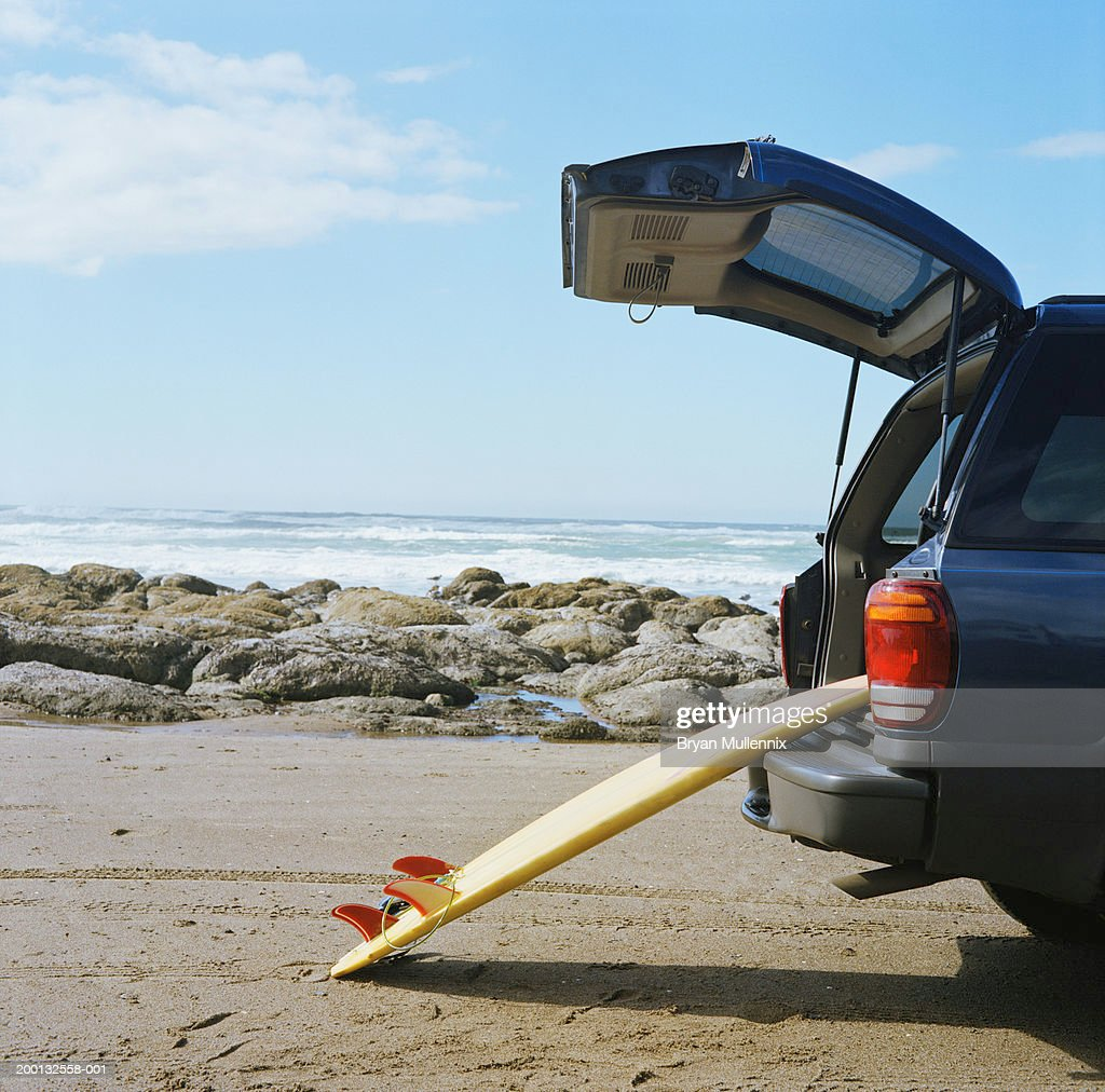 Surfboard leaning against open boot of SUV on beach : Stock Photo