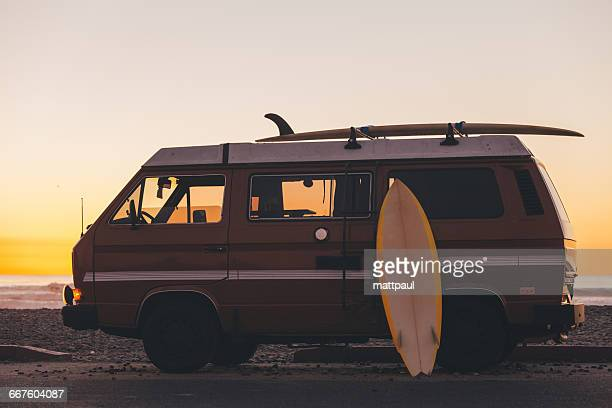 Surfboard leaning against Surf Bus at Sunset, California, America, USA