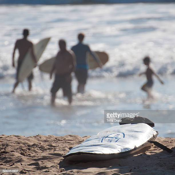 Surfboard on the beach with surfers and swimmers in the background at Imperial Beach California 08/15/14