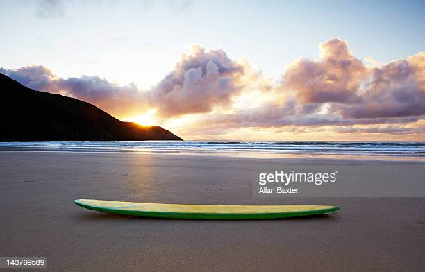 Surfboard resting on beach