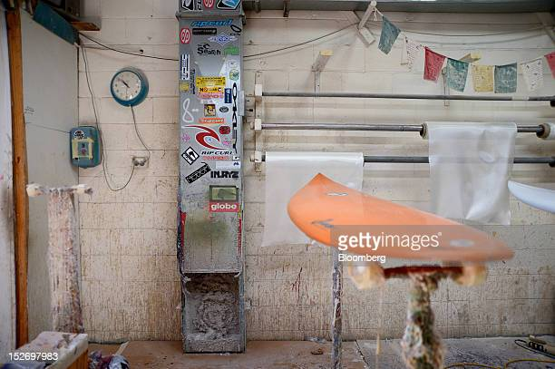 A surfboard rests on a stand as it awaits repair in the main workroom at the Moonlight Laminating Pty factory in Torquay Australia on Saturday Sept...