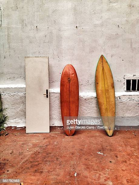 Surfboards And Broken Door Leaning On Wall