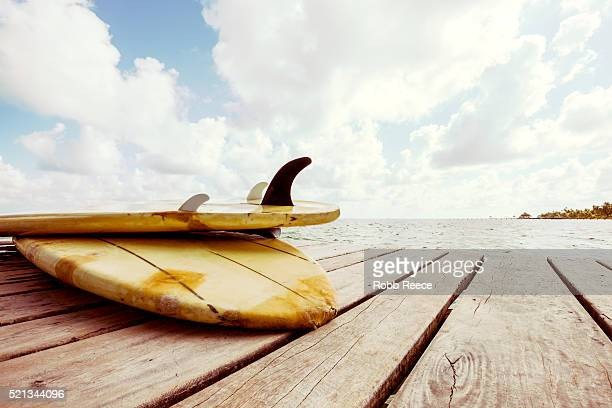 surfboards laying on a caribbean resort dock in belize - robb reece stock pictures, royalty-free photos & images