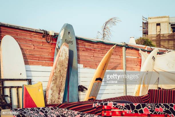 surfboards leaning on the wall illuminated by sunset light - tel aviv stock pictures, royalty-free photos & images