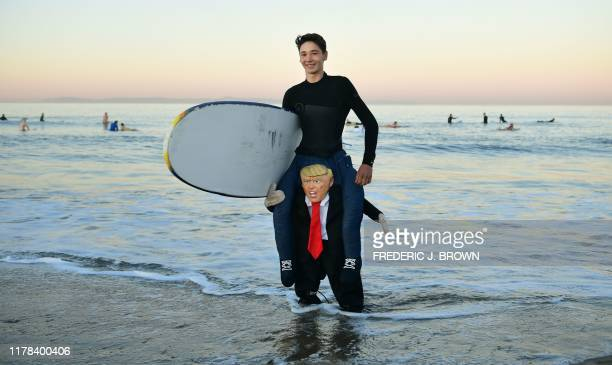 TOPSHOT Surfer Aj Cantu wears a costume appearing to sit on the shoulders of US president Donald Trump as surfers participate in the 16th Annual...