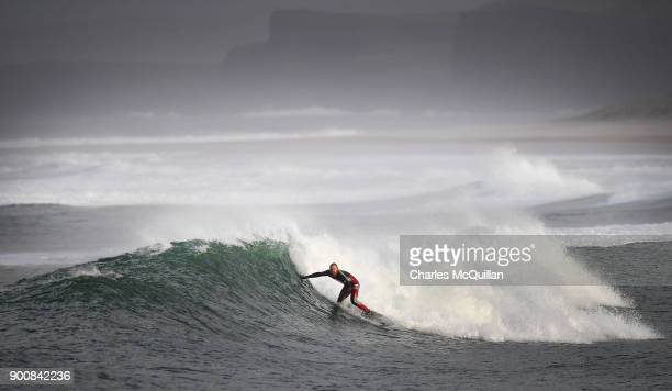 Surfer Al Mennie catches a wave at east strand beach after Storm Eleanor on January 3 2018 in Portrush Northern Ireland The Met Office has said that...
