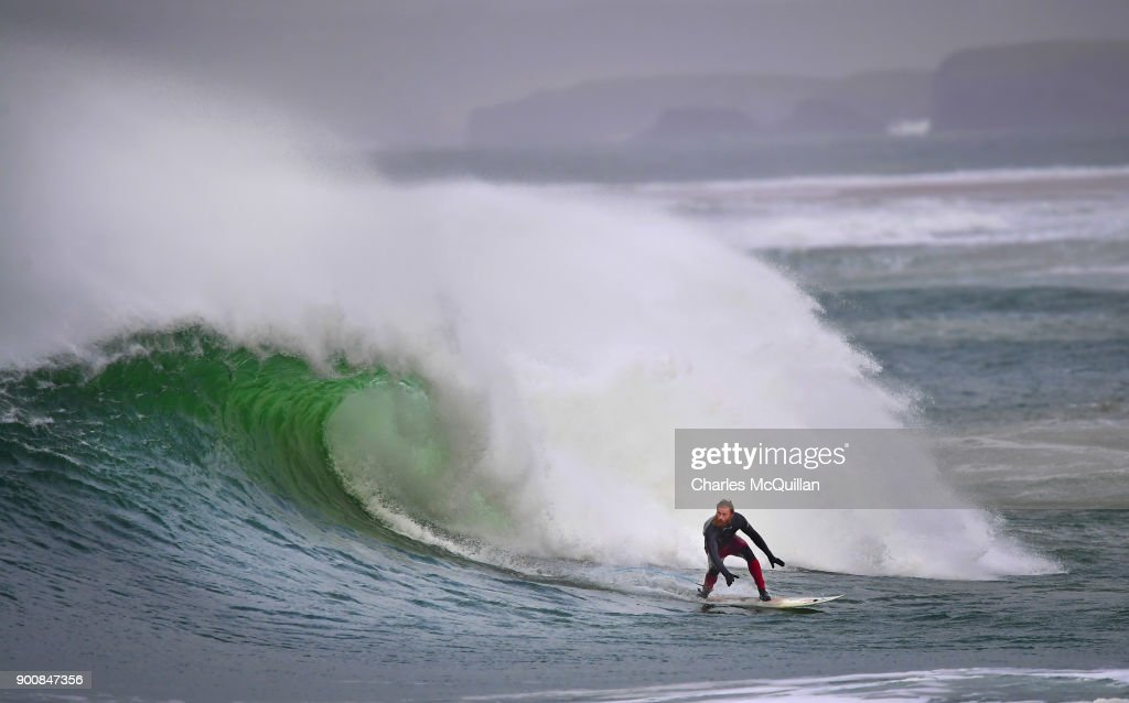 Surfer Al Mennie catches a wave at east strand beach after Storm Eleanor recorded winds of up to 90mph on January 3, 2018 in Portrush, Northern Ireland. The Met Office has said that Storm Eleanor is now over the North Sea but strong winds will continue to affect the province throughout much of Wednesday and a yellow wind warning will remain in place until 19:00 GMT.