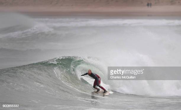 Surfer Al Mennie catches a wave at east strand beach after Storm Eleanor recorded winds of up to 90mph on January 3 2018 in Portrush Northern Ireland...