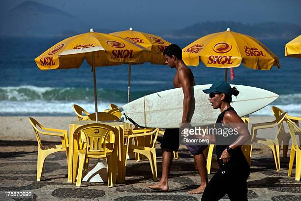 A surfer and a jogger at Ipanema beach pass by tables and umbrellas displaying the logo for Cia de Bebidas das Americass Skol brand beer in Rio de...