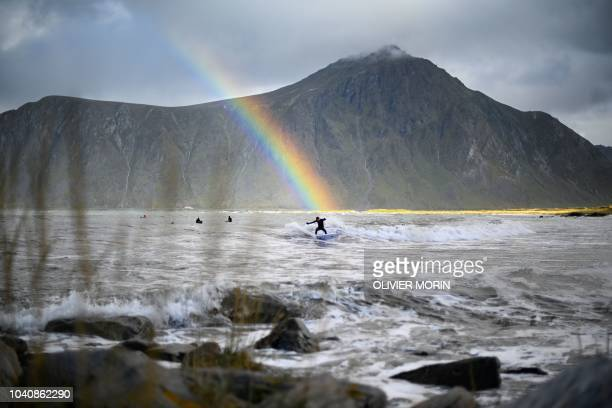 TOPSHOT Surfer Anker Olsen Frantzen of Norway rides a wave under a rainbow during a free surf session on September 26 in Flakstad northern Norway at...