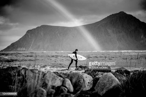 Surfer Anker Olsen Frantzen of Norway walks into the sea as a rainbow shines in the background Lofoten Masters 2018 is the most northern Surf contest...