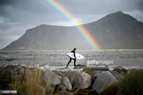 TOPSHOT Surfer Anker Olsen Frantzen of Norway walks to the water for a free surf session on September 26 in Flackstad Northern Norway the eve of the...