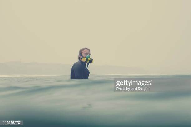surfer at sea and wearing a respirator during a bushfire smoke haze - forest fire stock pictures, royalty-free photos & images