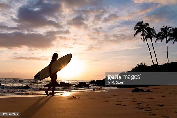 surfer at sunet walkinh on sand - maui - fotografias e filmes do acervo