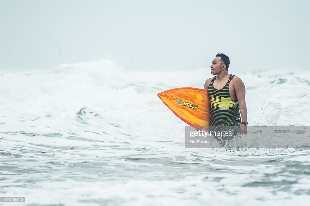 A surfer boy ready to surfing in Parangtritis Beach, Yogyakarta, Indonesia, on October 21, 2016. Despite high waves because of bad weather in Indonesia, Doplhin Parangtritis Surf Community keep surfing and this sport is quite interested by children and adults