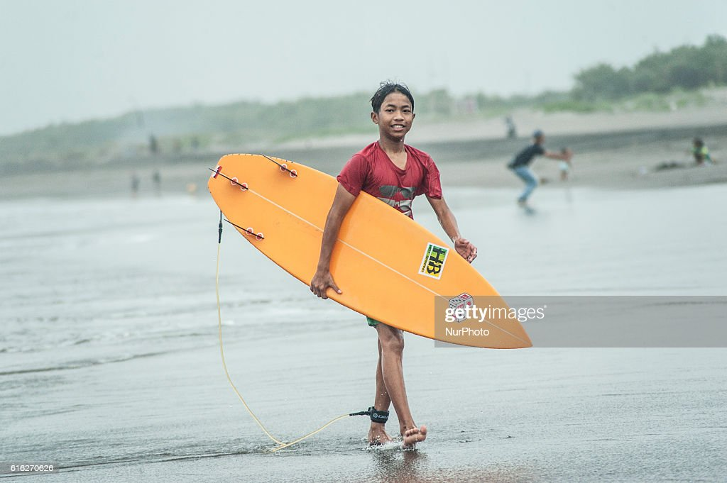 A surfer boy walk after surfing in Parangtritis Beach, Yogyakarta, Indonesia, on October 21, 2016. Despite high waves because of bad weather in Indonesia, Doplhin Parangtritis Surf Community keep surfing and this sport is quite interested by children and adults