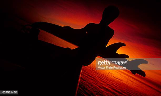 A surfer carries his board as the sun sets during the ongoing international surfing competition in Mundaka one of Europe's most famous waves northern...