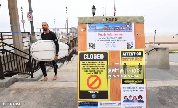 A surfer carrying his board walks past signs announcing closures and social distancing guidelines due to COVID19 at Huntington Beach California on...