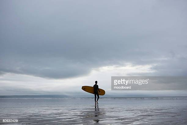 Surfer carrying surfboard on beach, back view