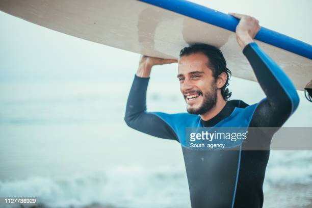 surfer carrying surfboard - surf stock pictures, royalty-free photos & images