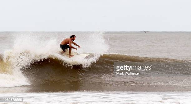 A surfer catches a ride at Folly Beach September 13 2018 in Charleston South Carolina United States Coastal cities in North Carolina South Carolina...