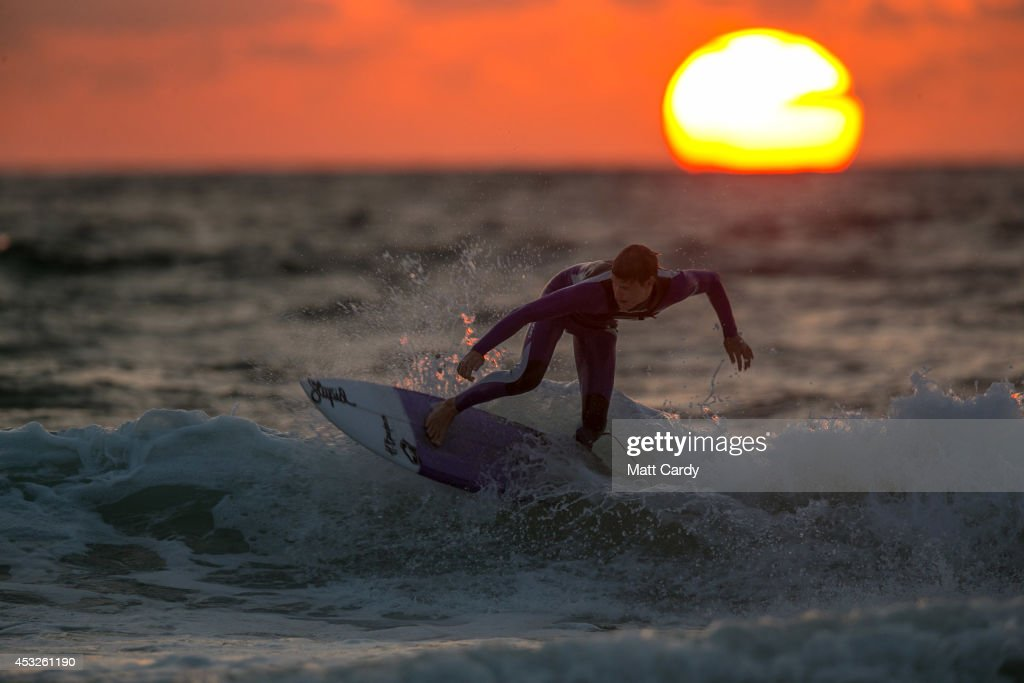 A surfer catches a wave as the sun sets on Fistral Beach on the first day of the Boardmasters surf and music festival in Newquay on August 6, 2014 in Cornwall, England. Since 1981, Newquay has been playing host to the Boardmasters surfing competition - which is part of a larger five-day surf, skate and music festival and has become a integral part of the continually popular British surf scene growing from humble beginnings, to one of the biggest events on the British surfing calendar. It now attracts professional surfers from across the globe to compete on the Cornish beach that is seen by many as the birthplace of modern British surfing.