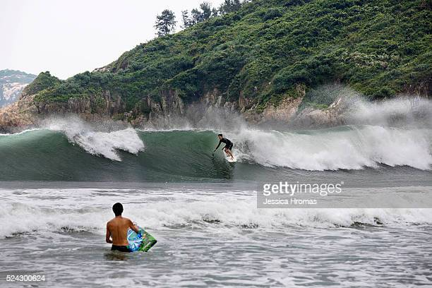 A surfer catches a wave at Big Wave Bay as typhoon Usagi is approaches on September 22 2013 in Hong Kong Hong Kong Typhoon Usagi is approaching the...