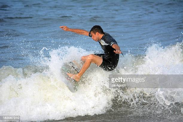 CONTENT] A surfer catches a wave at Seaside Park New Jersey on Aug 8 2013