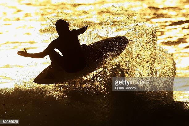 A surfer completes an aerial during an early morning surf at Winkipop Beach before the start of the Rip Curl Pro as part of the ASP World Tour held...