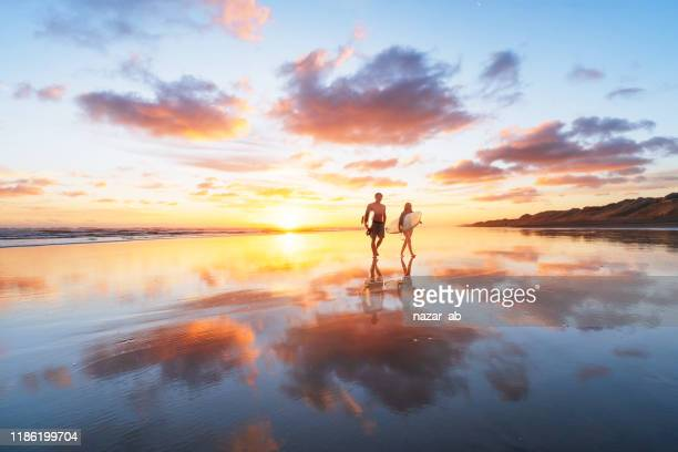surfer couple heading back after a long day at beach. - new zealand stock pictures, royalty-free photos & images