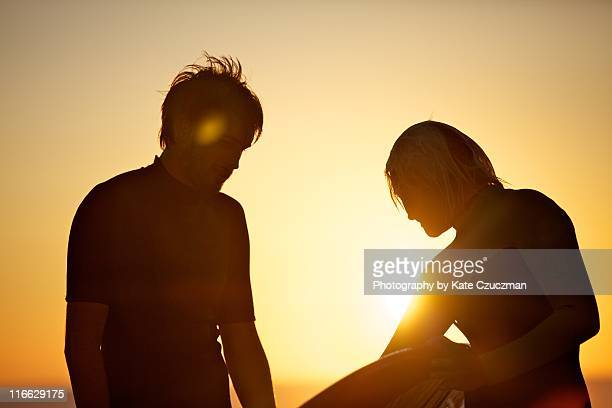 surfer couple on beach at sunset - aquitaine stock photos and pictures