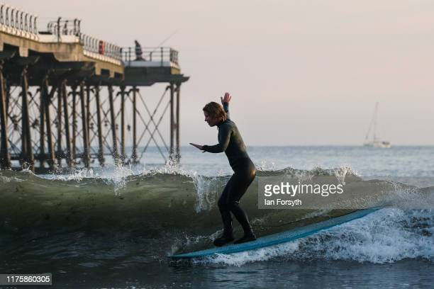 A surfer cross steps to the nose of her board as she surfs at sunrise on September 20 2019 in Saltburn By The Sea England Much of the country will be...