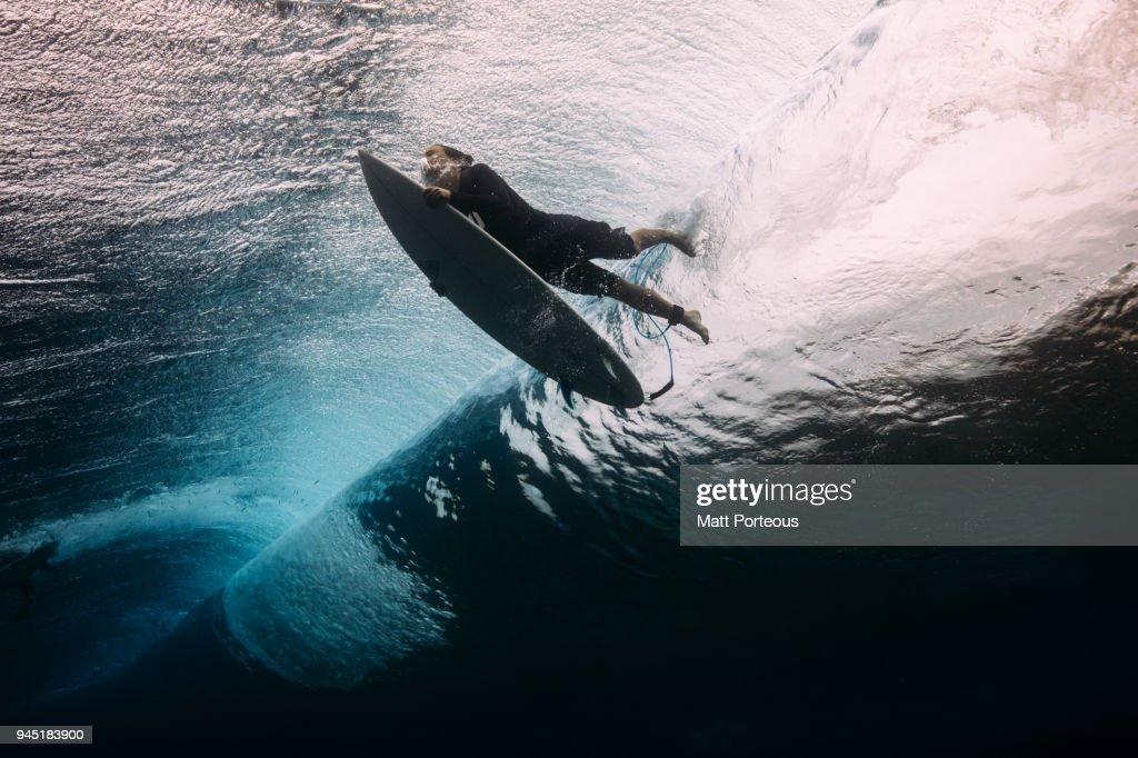 Surfer dives beneath a wave : Stock Photo