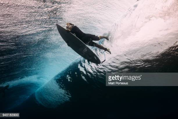 surfer dives beneath a wave - avontuur stockfoto's en -beelden
