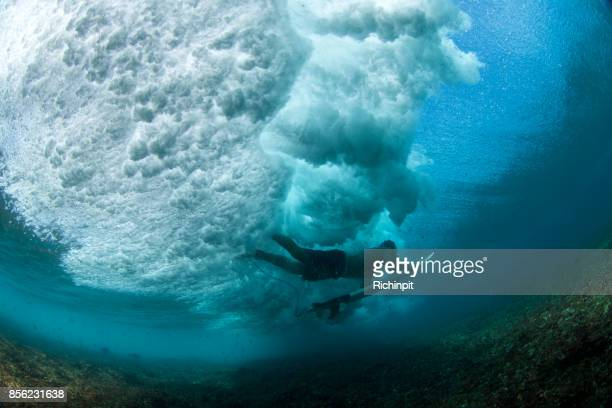 Surfer duckdives from below