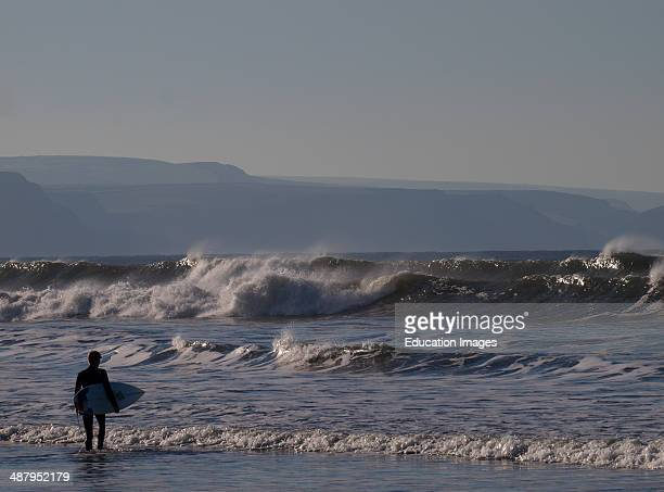 Surfer entering the sea in winter Bude Cornwall UK