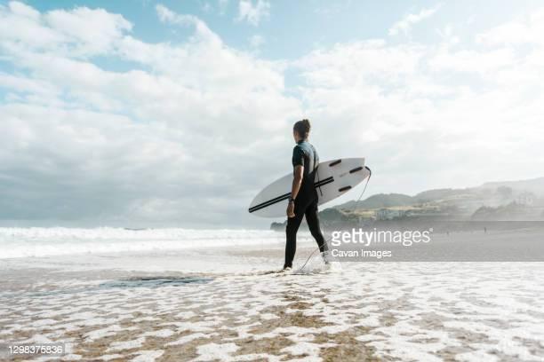 surfer entering the water in the basque country, spain, bilbao - pais vasco fotografías e imágenes de stock