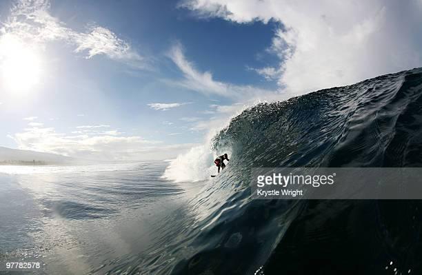 A surfer enters a barrel wave at Maninoa, Upolu, Samoa.