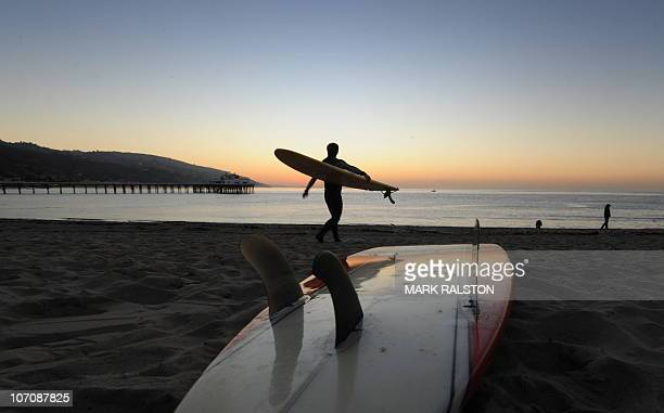 A surfer enters the water before tribal elder Mati Waiya from the Chumash Nation conducts the dedication ceremony for the iconic Malibu Surfrider...