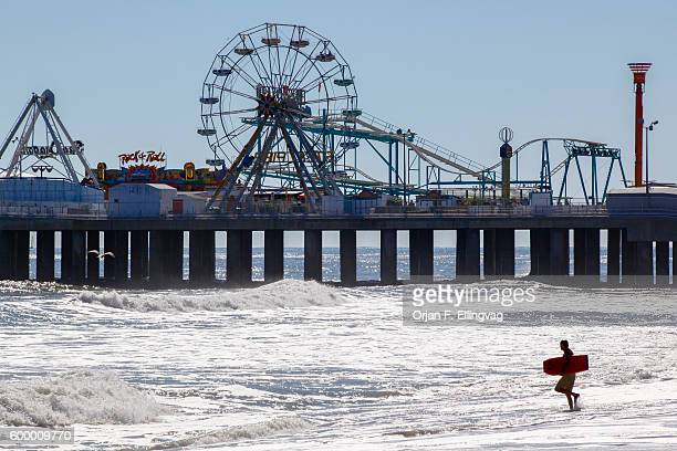 A surfer enters the water outside the Steel Pier in Atlantic City in October 2010 The city is in trouble after three casinos have closed in rapid...