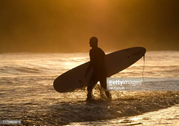 Surfer Evan Rogers enters the water for a surf as the sun rises over the beach on September 20 2019 in Saltburn By The Sea England Much of the...
