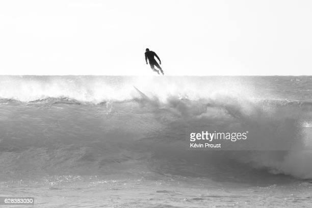 surfer falling off surfboard into breaking wave - personne humaine stock-fotos und bilder
