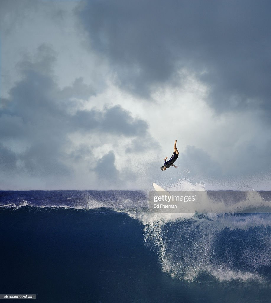 Surfer falling off surfboard into breaking wave : Stock Photo