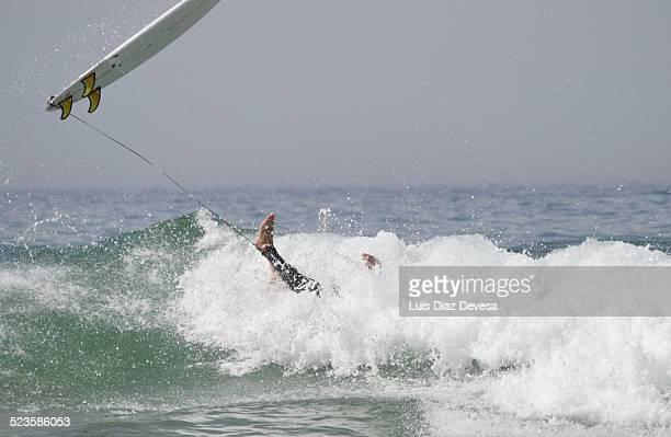 Surfer falling off surfboard